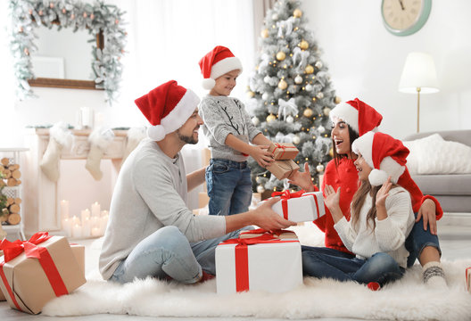 Happy family with children and Christmas gifts on floor at home