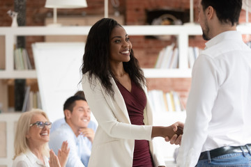 Male ceo handshake black female employee greeting at meeting