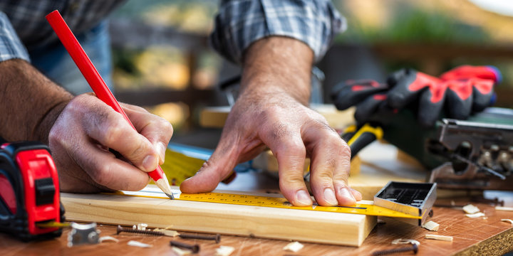 Adult carpenter craftsman with a pencil and the carpenter's square trace the cutting line on a wooden table. Construction industry, housework do it yourself. Stock photography.