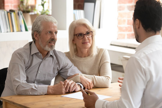 Happy mature couple meeting with financial consultant in office