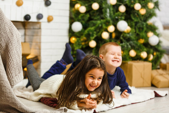 Happy little kids decorate Christmas tree in beautiful living room with traditional fire place. Children opening presents on Xmas eve.