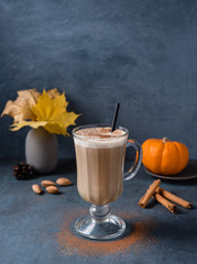 Spoed Foto op Canvas Milkshake spice coffee latte on glass with pumpkin, cinammon and nut on the dark blue table