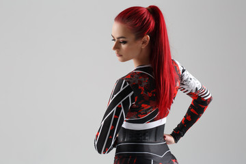 Beautiful sexy girl with red hair in a sports suit view from the back Isolated on a gray background.