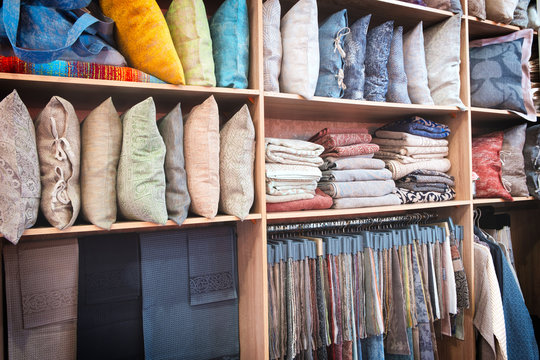 Bright pillows, towels, plaids, blankets and other home wear on shelves
