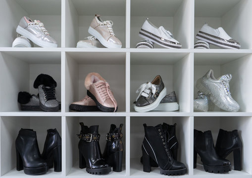 Fashion shoe of famouse brands is on the shelf. Сloset in which everything put in order. All shoes are folded neatly. Everything is in its place. Harmony. Showroom.