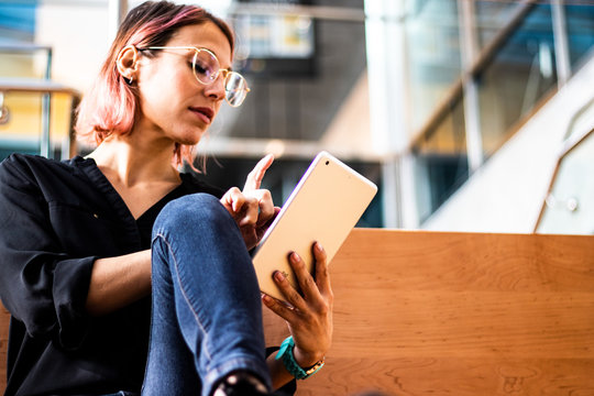 Smiling and pretty business woman using her digital tablet computer to read the news. She wears eyeglasses and blue jeans, casual style day. Technology app.