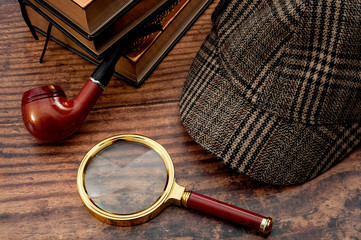 Fototapeta Literary fiction, police inspector, investigate crime and mystery story conceptual idea with sherlock holmes detective hat, smoking pipe, retro magnifying glass and book isolated on wood table top obraz