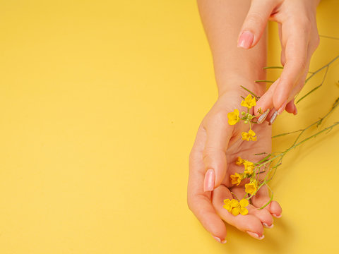 Hands art flower natural cosmetics women, yellow beautiful, spring flowers hand with bright contrast makeup, hand care. Fashion, creative beauty photo girl sitting at table,  yellow  background.
