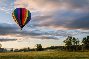 Poster Ballon Rainbow hot-air balloon floats over farm field on a late summer morning as the sun rises