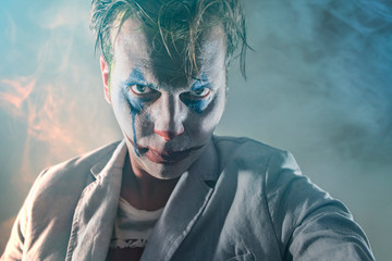 Halloween theme. The crazy joker face. Man in mime makeup cosplay