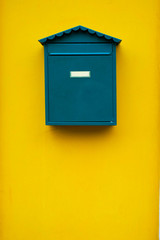 Elegant simple green mail box on a yellow wall.