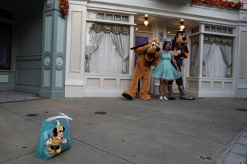 A visitor has her picture taken with Disney characters Goofy and Pluto at Hong Kong Disneyland in Hong Kong