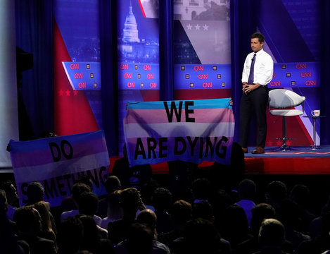 Democratic 2020 U.S. presidential candidate South Bend, Indiana Mayor Pete Buttigieg looks on as protesters hold transgender pride flags in a televised townhall on CNN dedicated to LGBTQ issues in Los Angeles, California