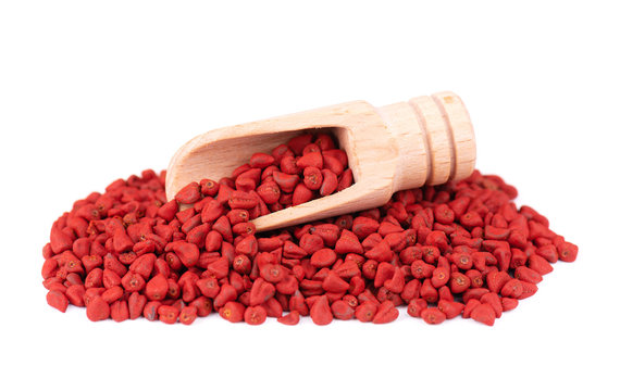 Annatto seeds, in the wooden spoon, isolated on white background. Achiote seeds, bixa orellana. Natural dye for cooking and food. Close-up.