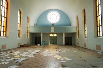 The interior of an old and abandoned church, light shining through the windows.