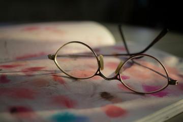 artist dirty vintage eye glasses on sketchbook color pastel art book