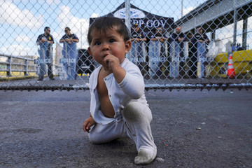 A Mexican baby is seen in front of the gates to the Gateway International Bridge in Matamoros