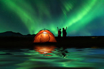 Papiers peints Europe du Nord Two Asian girls outdoor camping outdoor on Holiday with majestic Northern lights . Vacation ,Camping ,Travel Concepts.
