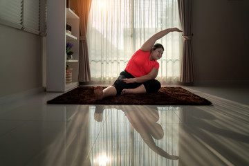 Asian Overweight woman exercising yoga Seated side bend pose alone on the floor in house, yoga meditation exercise at home. Fat women take care of health and want to lose weight concept..