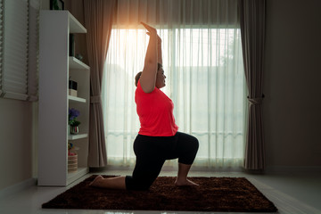 Asian Overweight woman exercising yoga High Lung pose alone on the floor in house, yoga meditation exercise at home. Fat women take care of health and want to lose weight concept..
