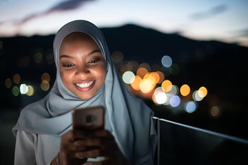 Young Muslim woman on  street at night using phone Fotomurales