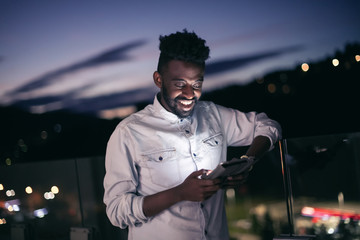 Young  Afro man on  street at night using phone Fotomurales
