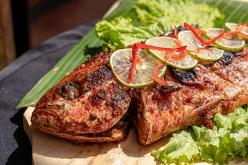 Fried fish with fresh green salad and lemon of Bali, Indonesia, closeup. Delicious roasted sea fish with lemon on wooden plate in restaurant