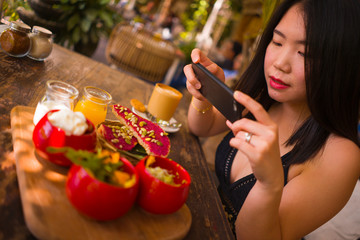 young beautiful Asian woman takes picture of food  with phone for internet blog. Chinese girl posting online photo for vegetarian organic social media