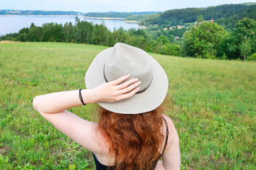 Young woman in a holiday hat looks at the beautiful landscape.