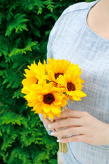 The woman is holding a bouquet of sunflowers.