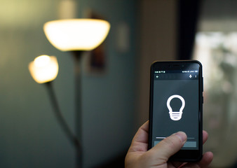 Smart home: man controlling lights with app on his phone.