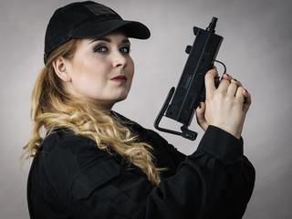 Woman holds gun in hands.