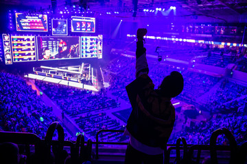 Big esports event. Video games fan on a tribune at tournament's arena with hands raised. Cheering for his favorite team.