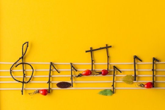 Musical notes conception. Wooden musical notes, berries and leaves.