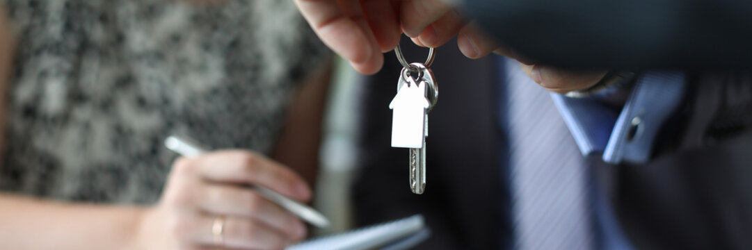 Focus on male hands holding keys to housing. Couple of married signing good deal of property purchase. Meeting and negotiations concept. Blurred background