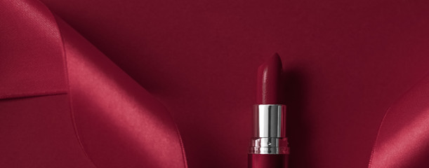 Luxury lipstick and silk ribbon on maroon holiday background, make-up and cosmetics flatlay for beauty brand product design Wall mural