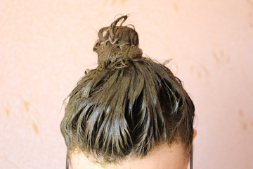 A process of dyeing hair with henna ecological product. Hair in a bun