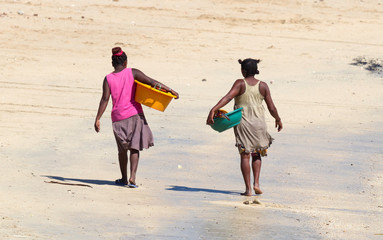 African women walking over the beach with laundry