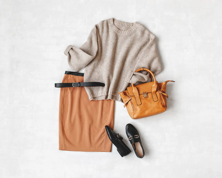 Brown midi pencil skirt, beige knitted oversize sweater, bag, belt, black loafers or flat shoes on grey background. Overhead view of women's casual day outfit. Flat lay, top view. Women clothes.