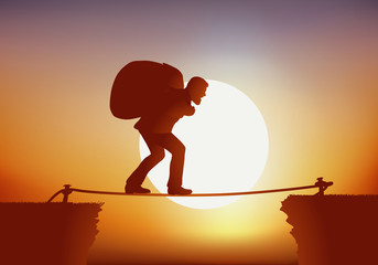 Concept d'un homme courageux, qui traverse un précipice en équilibre sur une corde, comme un funambule et transportant sur son dos un énorme sac.