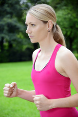 Sporty young blond woman running in the park
