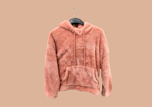 Pink Women Casual Cozy Sherpa Fleece Pile Hoodie Pullover on a hanger isolated on brown background. Composition of clothes. Flat lay, top view, copy space. Winter clothes pattern