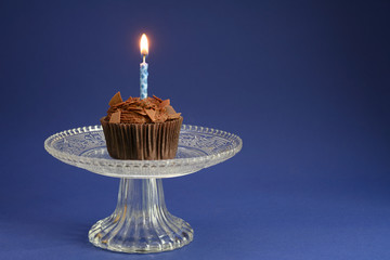 birthday cupcake with chocolate and a burning candle on a glass bowl, blue background with large copy space