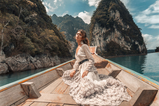 fashionable young model in elegant dress on boat at the lake