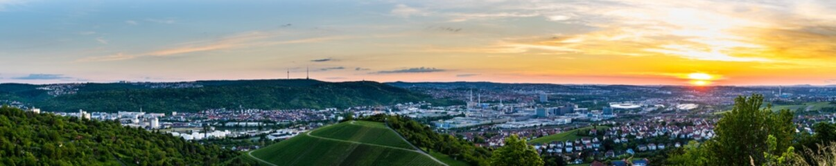 Germany, XXL panorama view over beautiful downtown of stuttgart city in neckar valley between green mountains in warm orange sunset mood