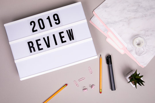 2019 review concept. White lightbox on a gray office desk