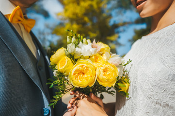 Bride and groom hold a bridal bouquet of yellow roses in their hands in autumn sunny day.