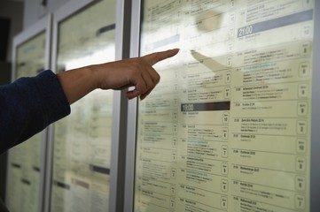 Young woman traveling, pointing finger on train timetable in railway station