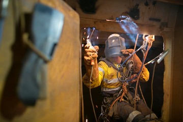 Rope access welder wearing fully safety uniform fall protection helmet, welding glove harness, commencing welding chute repair in confined space construction mine site Perth Pilbara region Australia