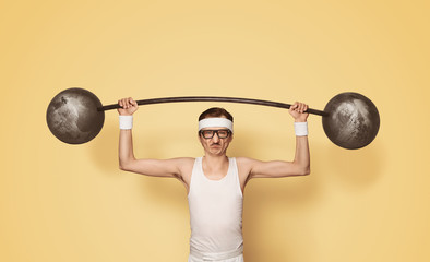 Funny retro sport nerd lifting weights over yellow background with copy space